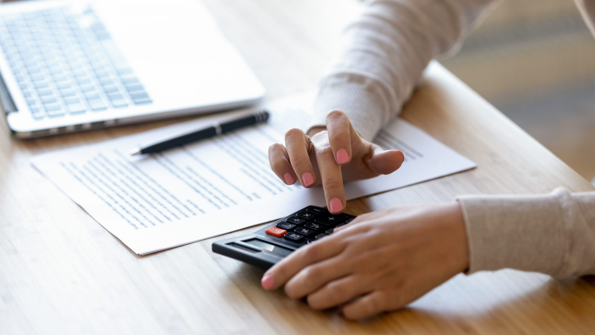 Young,Woman,Using,Calculator,,Calculating,Finance,At,Workplace,,Female,Hands